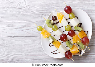 Tropical fruit on skewers with chocolate. horizontal  top view