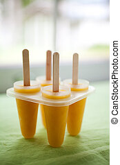 Tropical fruit popsicle - Yellow popsicles with tropical...