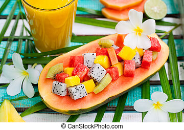 Tropical fruit salad in half of papaya with mango juice, smoothie on colorful wooden background. Top view