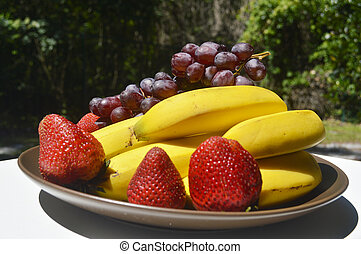 Tropical fruits as banana mango strawberries red grapes in a...