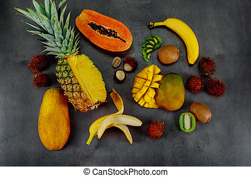 Tropical fruits assortment on a dark wood background with top view.