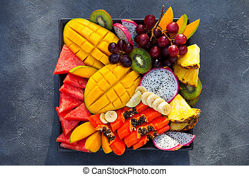 Tropical fruits assortment on a plate. Grey background. Close up. Top view.