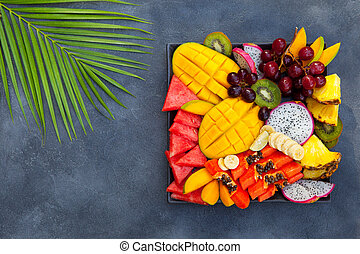 Tropical fruits assortment on a plate. Grey background. Copy space. Top view.