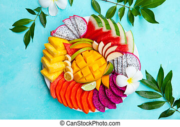 Tropical fruits assortment on a plate with frangipani flowers. Blue background. Top view. Copy space.