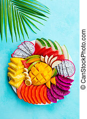 Tropical fruits assortment on a white plate with palm leaf. Blue background. Top view.