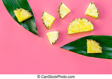 Tropical fruits background. Pinneapple slices in front of big leaves on pink background top view copyspace