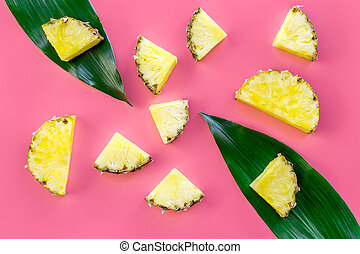 Tropical fruits background. Pinneapple slices in front of big leaves on pink background top view