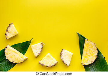 Tropical fruits background. Pinneapple slices in front of big leaves on yellow background top view copyspace