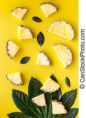 Tropical fruits background. Pinneapple slices in front of small and big leaves on yellow background top view