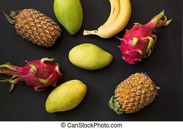 Tropical fruits pineapple, banana, dragon fruit and mango on black. Top view. Flat lay.