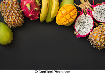 Tropical fruits pineapple, banana, dragon fruit and mango on black. Top view.