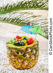 Tropical fruits salad in pineapple with cocktail umbrellas