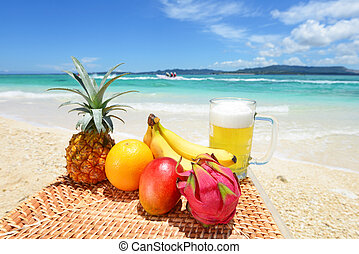 Tropical fruits with beer on the sandy beach