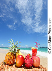 Tropical fruits with juice on the sandy beach