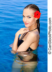 Tropical girl with flower on her ear posing in swimming pool