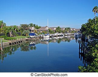 Tropical Homes on Canal with Boats and Docks.
