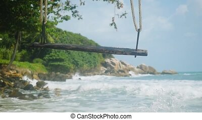 Tropical Island Beach and Swing. Splashing waves in the Sea...