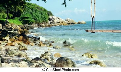 Tropical Island Beach and Tree Swing. Splashing waves in the...