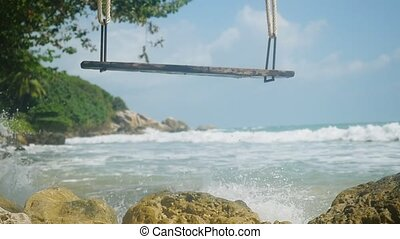 Tropical Island Beach with swing. Splashing waves in the Sea in slow motion.