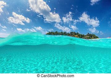 Tropical island on Indian Ocean, Maldives. Half underwater shot