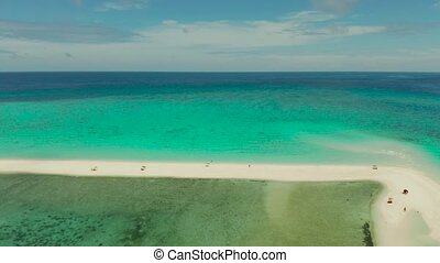 Beautiful beach on tropical island surrounded by coral reef, sandy bar with tourists, top view. Sandbar Atoll. Summer and travel vacation concept, Camiguin, Philippines.