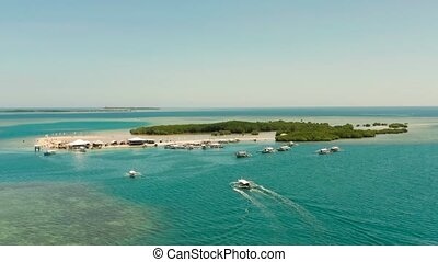 Luli island and sandy beach with tourists, sand bar surrounded by coral reef and blue sea in the honda bay, aerial drone. Tropical island and coral reef. Summer and travel vacation concept, Philippines, Palawan