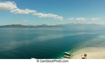 Tropical island and sandy beach with tourists surrounded by coral reef and blue sea in honda bay, aerial view. Island with sand bar and coral reef. starfish island. Summer and travel vacation concept, Philippines, Palawan