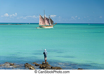 Fishing in the tropics with a magnificent sailboat passing by.