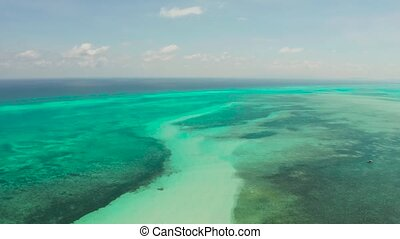 Flying over the sea with turquoise water, atoll and coral reef, aerial view. Balabac, Palawan, Philippines. Summer and travel vacation concept.