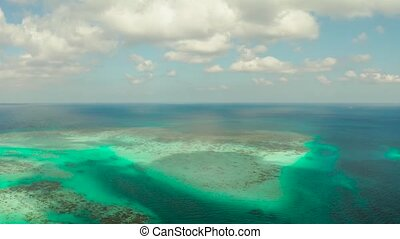 Atoll with azure clear water and coral reef on the background of blue sky and clouds, top view. Balabac, Palawan, Philippines. Summer and travel vacation concept.
