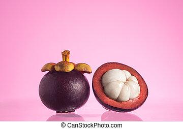 Tropical mangosteen fruits, queen of fruits, studio shot on pink background