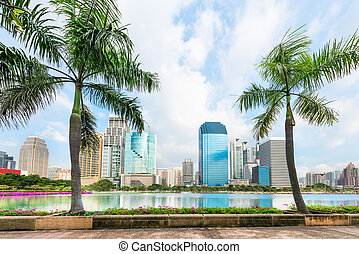 Tropical modern city with palm trees and lake on front