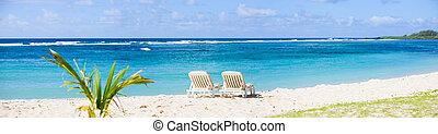 Tropical Paradise. Sun beds on tropical white sand beach.