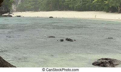 tropical rain on island beach in azure sea