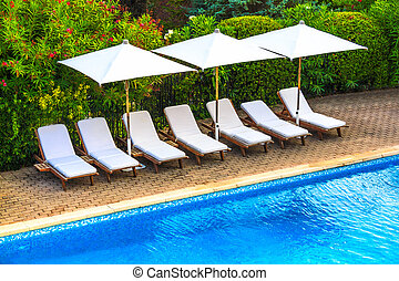 Tropical resort sun chairs and swimming pool