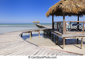 View of wooden walkway on tropical cuban beach at cayo coco