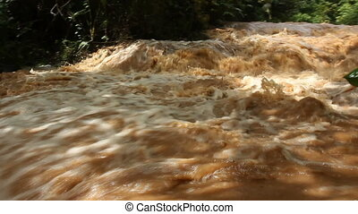 Tropical river in flood - Mud and water pouring down a...