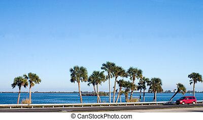 Tropical Roadside - Road running alongside blue water and ...