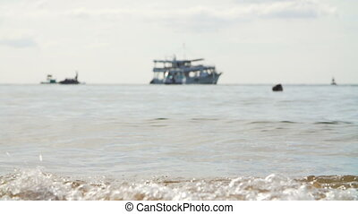 Tropical sand beach with a boat on horizon - Tidal bore on a...