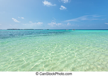 Tropical sandy beach with white sand under clear water and sky