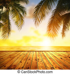 Tropical sea and leaves of coconut palm tree at sunset.
