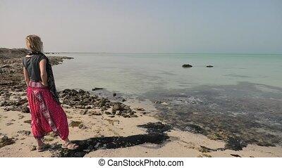 Tropical sea in Persian Gulf - Caucasian woman looking...