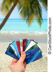 tropical spending - hand holding different plastic cards...
