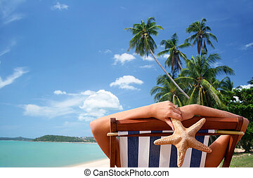 Tropical Sunbather - Woman in deckchair with tropical view...