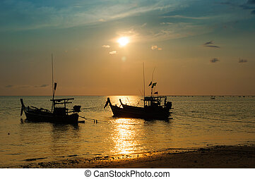 Tropical sunset and boat on the beach