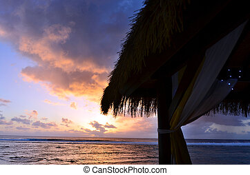 Tropical sunset over a beach bungalow