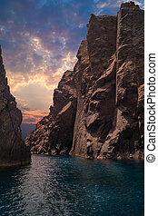Tropical sunset throught high rocks in Aegean Sea, Greece