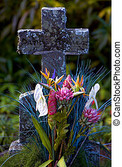 tropical flowers decorating old stone cross grave marker in kauai