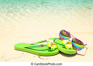 Tropical vacation concept—Green flip-flops and sunglasses on a sandy ocean beach with small fish in the water