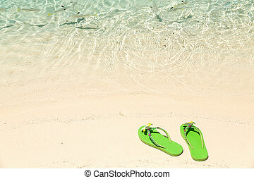 Tropical vacation concept—Green flip-flops on a sandy ocean beach with small fish in the water